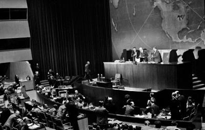 Foto: ©ONU/AF. O diplomata gaúcho Oswaldo Aranha, na foto, no centro do púlpito, exercendo a função de Presidente da Segunda Sessão da Assembleia Geral das Nações Unidas é aplaudido de pé pelos delegados presentes, após seu discurso no encerramento da discussão sobre o Plano de Partilha da Palestina, no dia 29 de novembro de 1947. À sua esquerda, o Secretário-Geral da ONU, Trygve Lie, e à sua direita, Andrew W. Cordier, Assistente Executivo do Secretário-Geral. Atualmente, as Nações Unidas comemoram, todos os anos, no dia 29 de novembro, o Dia Internacional de Solidariedade com o Povo Palestino. O Plano de Partilha da Palestina foi elaborado pelo UNSCOP (Comitê Especial das Nações Unidas para a Palestina), consistia na divisão do território em dois Estados independentes: um judeu e um palestino, com a cidade de Jerusalém sob controle internacional. Na ocasião, adotou-se a resolução 181, que contou com 33 votos a favor, 13 contra, 10 abstenções e uma ausência. Os palestinos e os Estados árabes não aceitaram o Plano, que foi aceito pelos judeus. Em 14 de maio de 1948, o mandato britânico na Palestina acabou e no mesmo dia foi proclamado o Estado de Israel. Hostilidades entre os países árabes e a comunidade judaica irromperam imediatamente. No dia seguinte, as tropas dos vizinhos Estados árabes entraram no território para ajudar os árabes palestinos. As hostilidades somente cessaram com a criação, pelo Conselho de Segurança da ONU, da Organização das Nações Unidas de Supervisão da Trégua (UNTSO), em 1948, a primeira força de paz da ONU, que está em funcionamento até os dias de hoje.