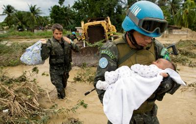 Foto: ©ONU/Marco Dormino. Membros do batalhão brasileiro da Missão das Nações Unidas para a Estabilização no Haiti (MINUSTAH) resgatam uma criança das inundações causadas pelas chuvas da tempestade tropical Noel que devastou o país em outubro de 2007. O Brasil é o maior contribuinte de tropas para a Missão. De 2004 a fevereiro de 2010, o País manteve um contingente de 1.200 militares, com rotação semestral. Após o terremoto, que atingiu o país em janeiro deste ano, passou a manter contingente maior, formado atualmente por 2.216 soldados e oficiais (dados de julho de 2010). Desde o início da participação brasileira até hoje, mais de 13 mil militares brasileiros serviram no Haiti. Desde 2004, o comando militar de todas as tropas que compõem a MINUSTAH, provenientes de 19 países, é exercido por generais brasileiros. Reforçada após o terremoto, a Missão conta com 8.766 militares, 3.082 policiais e 1.920 funcionários civis (dados de agosto de 2010).